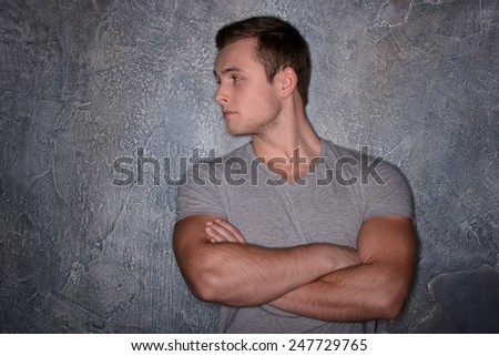 Handsome and confident. Young handsome man looking away and keeping his eyes crossed while standing against dark wall  - stock photo