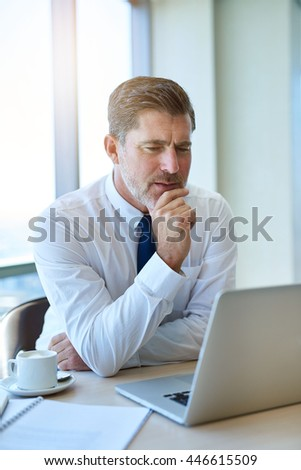 Handsome and mature businessman sitting at a desk with a cup of coffee and holding his chin, while looking seriously at information on the screen of his laptop computer