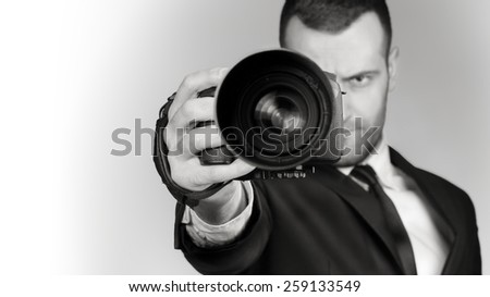 Handsome and Professional Photographer in Business Suit. Serial and Seriously Shutter! Black and white - stock photo