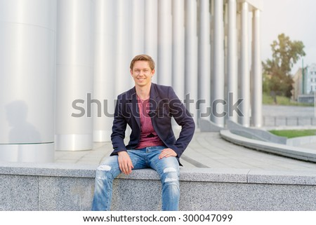 Handsome and relaxed. Young man in casual wear sitting outdoors. - stock photo
