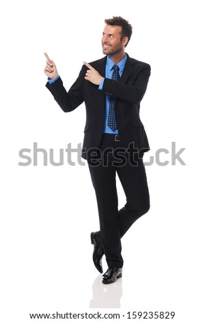 Handsome and smiling businessman pointing at copy space    - stock photo
