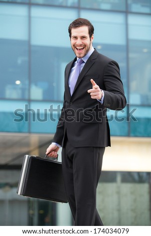 handsome and successful businessman smiling in front of an office building with a briefcase in his hand - stock photo