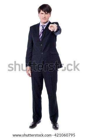 Handsome angry businessman pointing finger at you.
