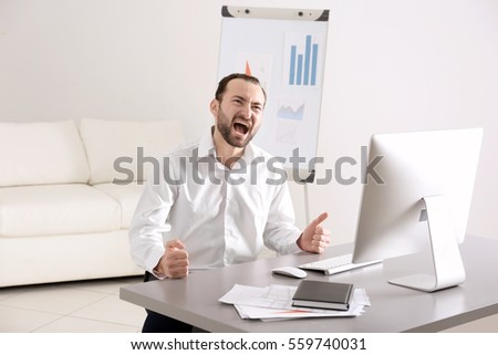 Handsome angry man sitting at table in office