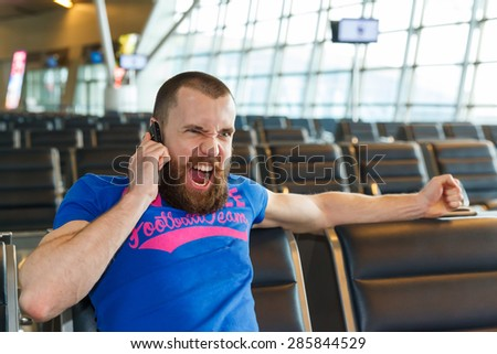 handsome angry young man with blond short hair talking on the phone, sitting on a chair with things at the airport waiting for his flight - stock photo