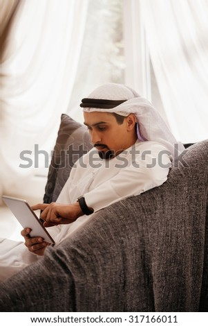 Handsome Arabian Male Sitting On Sofa And Using Digital Tablet