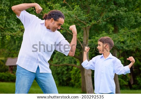 Handsome arabian man and his son showing muscles.