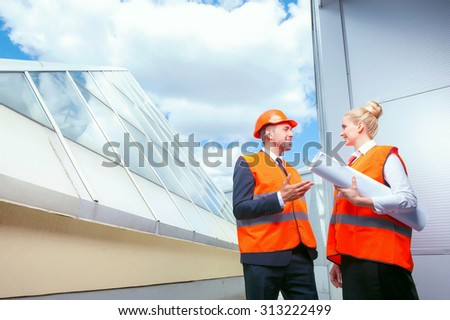 Handsome architect and his colleague are talking about new project. They are standing outdoors and smiling. The workers are looking at each other with inspirations. The woman is holding a blueprint - stock photo