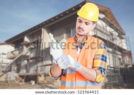 Handsome architect getting ready for work and putting gloves on while standing in front of renovated house