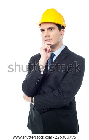 Handsome architect hand holding the chin, looking up - stock photo