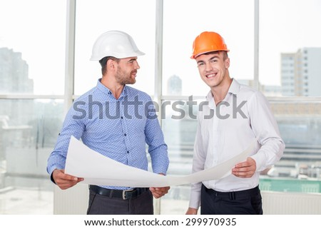 Handsome architect is showing sketching of construction to a builder. The foreman likes his idea. He is smiling with satisfaction. The architect is looking at him happily - stock photo