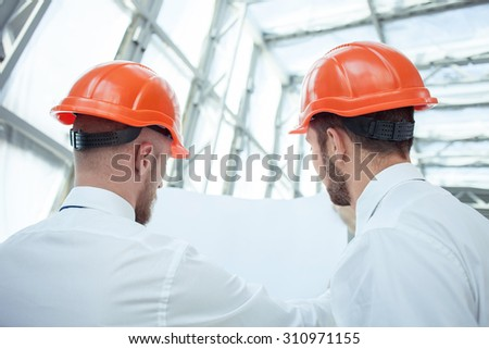 Handsome architects are looking at the blueprint with seriousness. They are discussing their new project with inspirations. Focus on male back - stock photo
