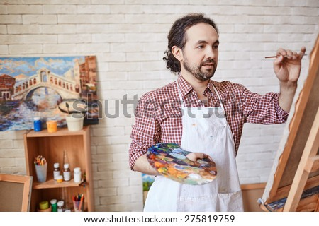 Handsome artist with paintbrush and palette painting on canvas - stock photo