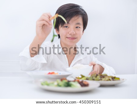 Handsome Asian boy eating food with chopsticks