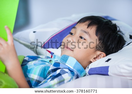 Handsome asian boy reading a book lying on bed in bedroom. Children read and study, education concept.