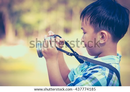 Handsome asian boy taking photo by vintage film camera on blurred nature background, on summer in the day time. Outdoors Vintage tone. - stock photo