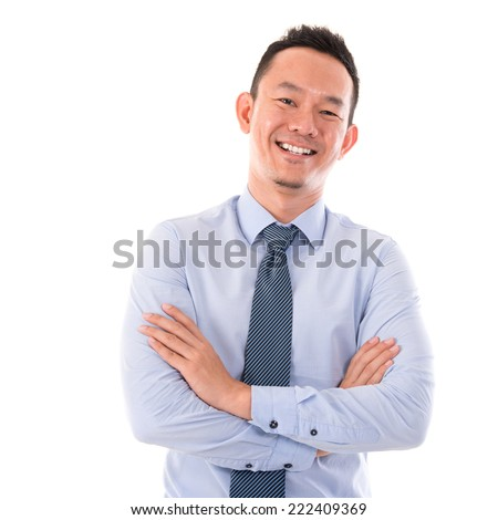 Handsome Asian business man smiling, standing isolated over white background. - stock photo
