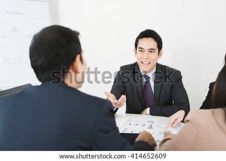Handsome Asian businessman sharing opinion at the meeting