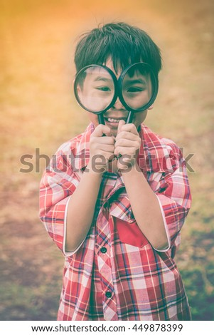 Handsome asian child enjoying with magnifying glass at park on vacation. Education concept. Outdoors in the day time with bright sunlight. Warm tone and vintage picture style. - stock photo