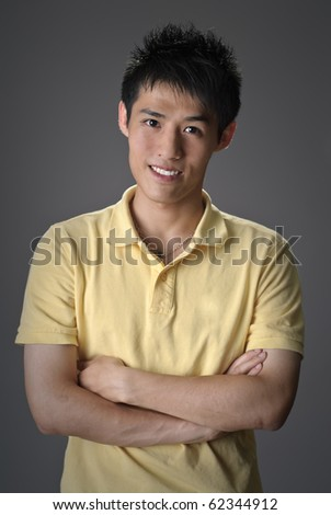 Handsome Asian guy, closeup portrait with smiling expression over studio gray background. - stock photo