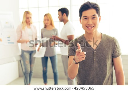 Handsome Asian guy is smiling, looking and pointing at camera, in the background his colleagues are discussing business affairs - stock photo
