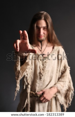 Handsome asian man with long hair makes a gesture blessing.