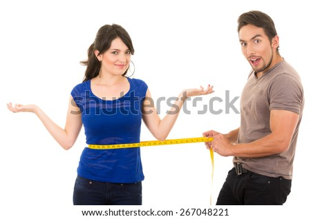 handsome astonished man holding measuring tape around thin fit young girl's waist concept of dieting fitness weightloss  isolated on white