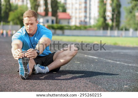 Handsome athlete is sitting on the road. He is stretching one leg forward while another leg is bent. He stretches himself with seriousness. There is copy space in right side - stock photo