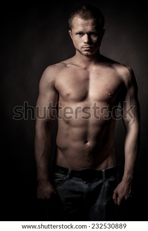 Handsome athlete on a black background - stock photo
