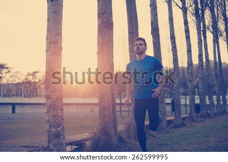 Handsome athlete running in the park along trees at sunset (little motion blur, intentional sun glare and vintage color) - stock photo