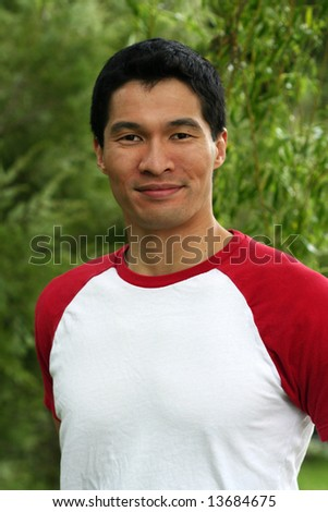 Handsome, athletic Asian model smiling in an outdoor setting.