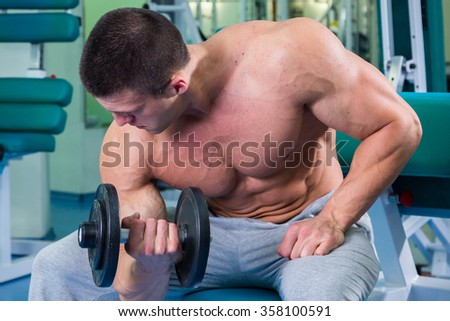 Handsome, athletic, confident man in the gym. bodybuilding pose