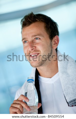 Handsome athletic man at the gym holding a bottle of water - stock photo