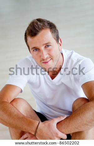 Handsome athletic man at the gym smiling - stock photo