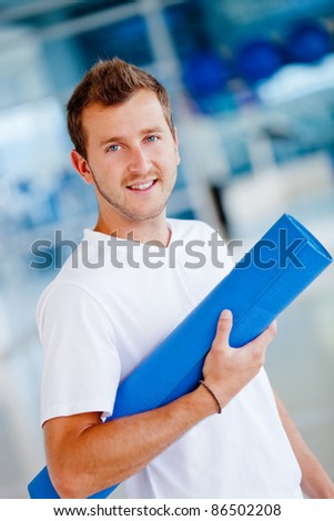 Handsome athletic man at the gym with a mat - stock photo