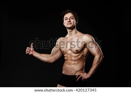Handsome athletic man  in unbuttoned trousers. Strong bodybuilder with six pack, perfect abs, shoulders, biceps, triceps and chest. Great fitness body. Ideal for commercial. Gray background
