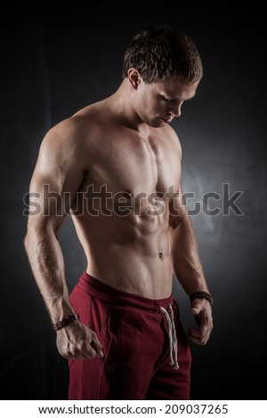 Handsome athletic man posing on dark background