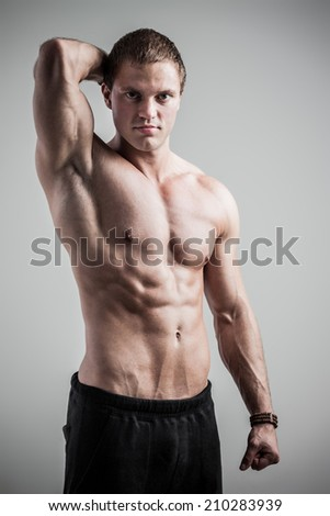 Handsome athletic man posing on gray background