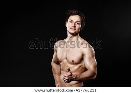 Handsome athletic man showing thumb-up in black pants. Strong bodybuilder with six pack, perfect abs, shoulders, biceps, triceps and chest. Great fitness body. Ideal for commercial. black background