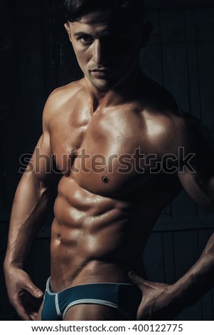 Handsome athletic sexual young guy bodybuilder brunet with strong muscular torso perfect cool six-pack abdominal muscles wearing fashion underwear looking straight posing on dark background closeup  - stock photo