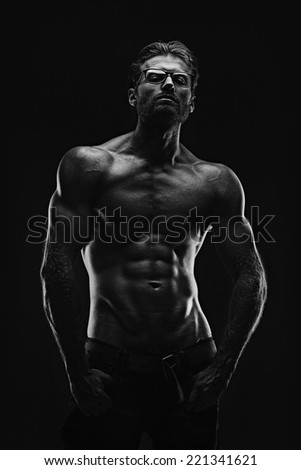 Handsome athletic young aesthetic man isolated on black. Black and white