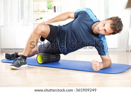 Handsome Athletic Young Man Doing Side Planking with Foam Roller on his Thigh.