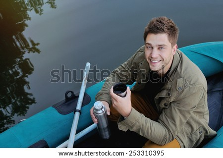 handsome attractive man on the boat at the lake on beautiful nature background, relax concept - stock photo