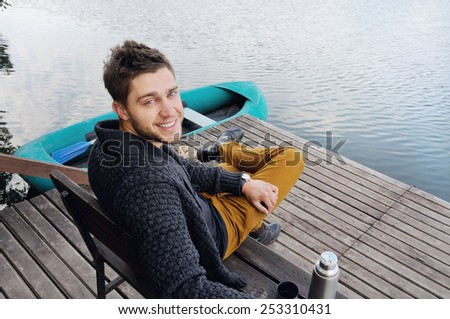 handsome attractive man on the wooden pier at the lake on beautiful nature background, relax concept - stock photo