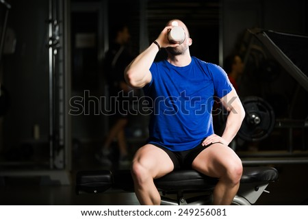 Handsome attractive muscular man after training in the gym.Young muscular man drinking protein shake on Scott bench after doing exercises - stock photo