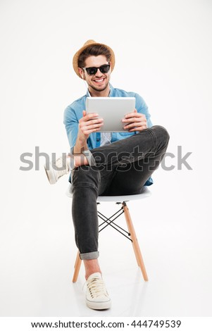 Handsome attractive smiling happy joyful young male using tablet and sitting on the chair isolated on the white background - stock photo