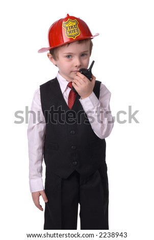 handsome attractive young boy dressed as a fire chief- in suit with helmit and walkie-talkie in hand on white background.