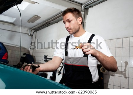 Handsome auto mechanic checking engine oil in car service. - stock photo