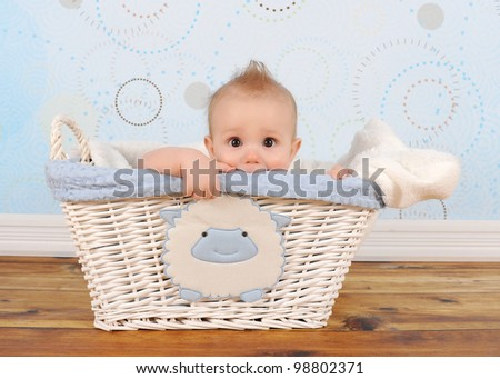 handsome baby boy playfully peeking out of wicker basket - stock photo