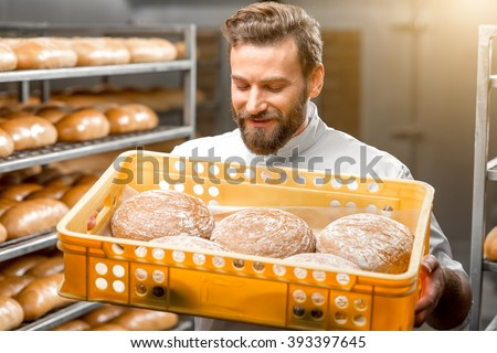 Handsome baker holding box full of freshly baked buckweat breads at the manufacturing - stock photo